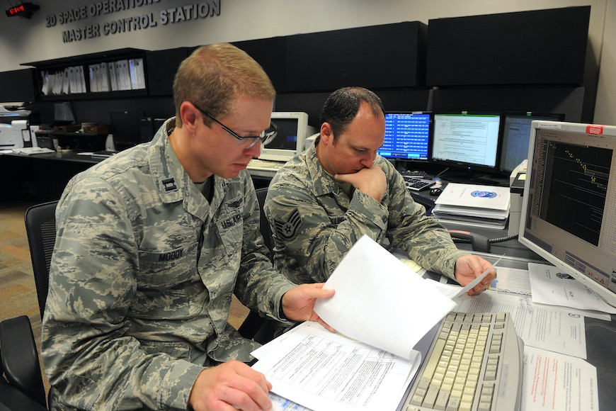 Capt. Adam Moody, 2nd Space Operations Squadron Global Positioning System Operations Support flight commander, and Staff Sgt. Carl Ellinger, 2 SOPS GPS mission chief, review a checklist of procedures for a transfer operation at Schriever Air Force Base, Colorado (U.S. Air Force photo/Dennis Rogers)